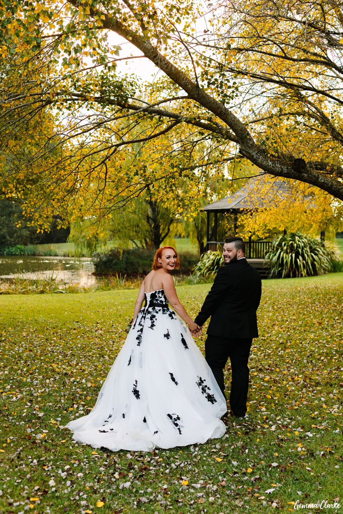 Stunning autumn colours as the bride and groom walk across a yellow leaf covered lawn toward the gazebo at this Briars Country Lodge Wedding
