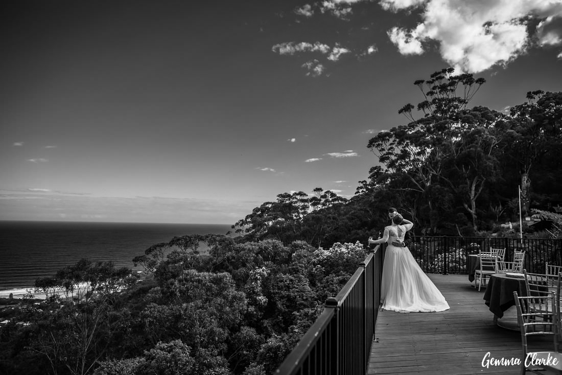 This Tumbling Waters Retreat Wedding in black and white as the couple have a drink and a cuddle on the balcony overlooking Stanwell Park Beach