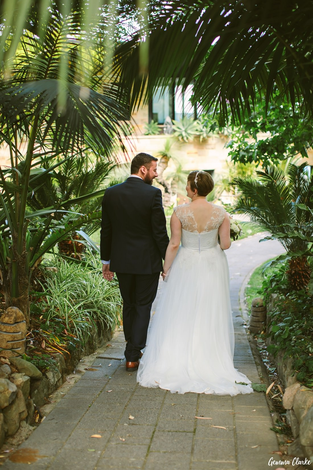 Kaisa and David walk hand in hand through a fern covered walkway at this Tumbling Waters Retreat Wedding