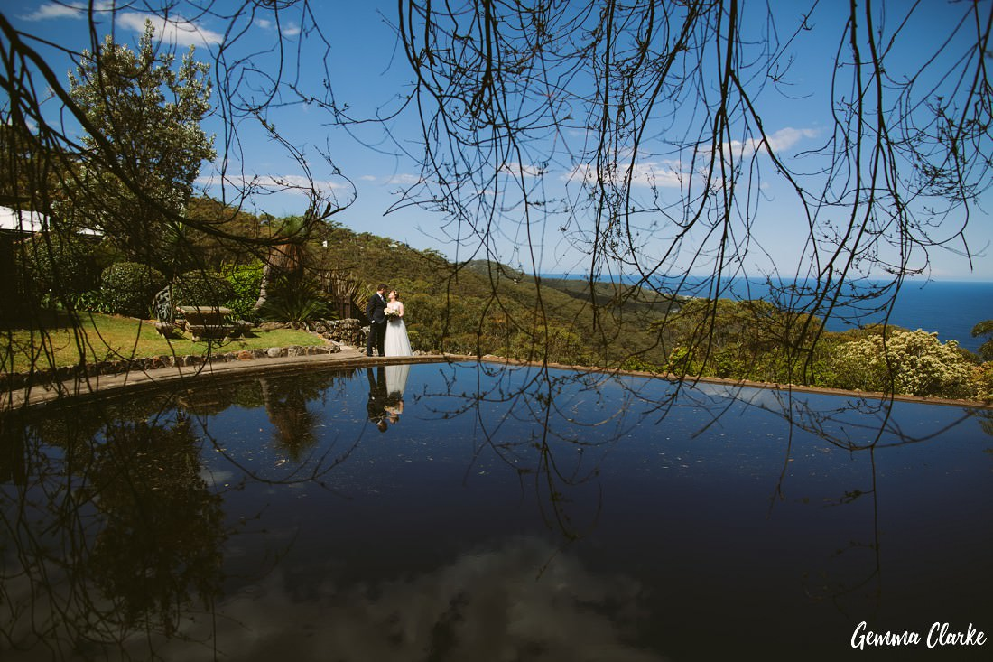 View across the pond as the couple look to each other in the background with the overhanging branches framing them at their Tumbling Waters Retreat Wedding