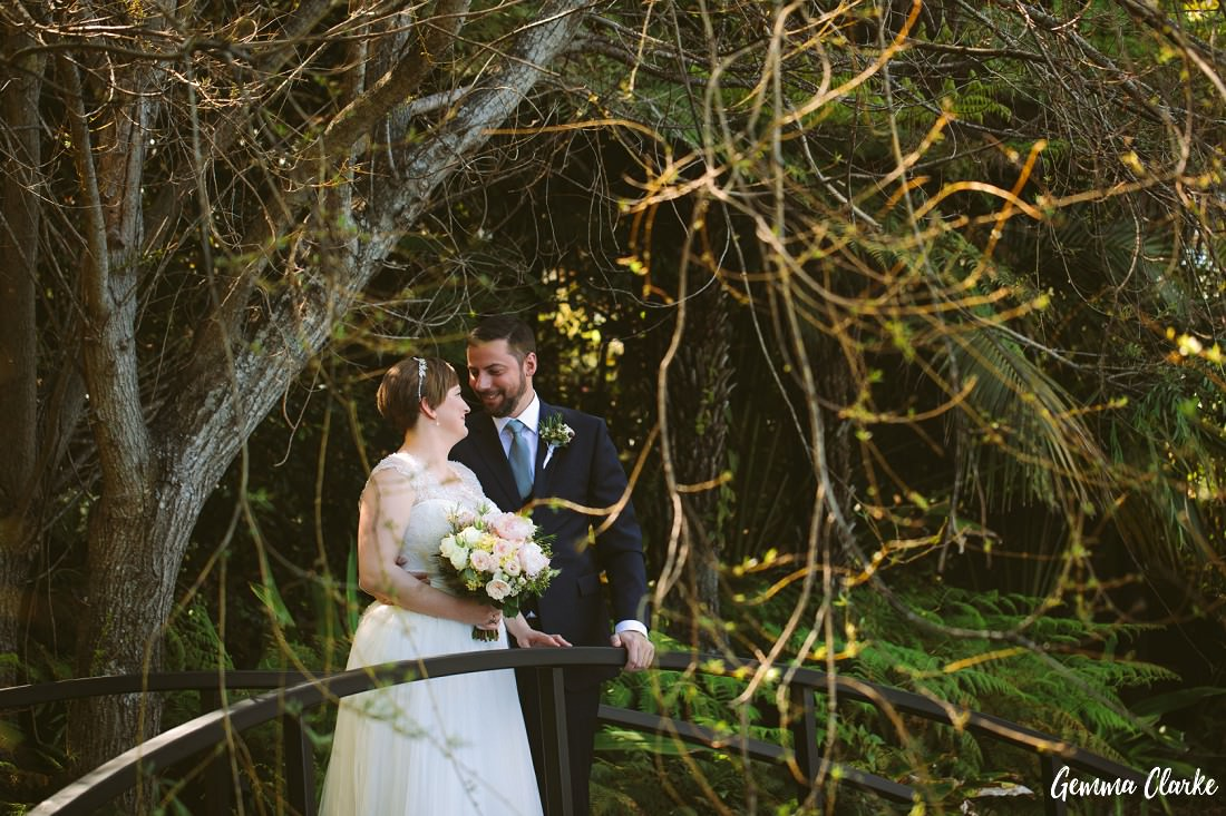 Bride and Groom stand on the bridge as they look dreamingly into each other's eyes at their Tumbling Waters Retreat Wedding