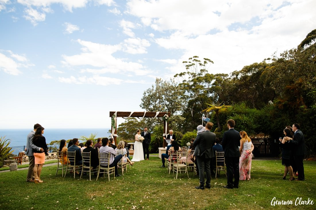 Small number of guests enjoy the ceremony of Kaisa and David at this Tumbling Waters Retreat Wedding