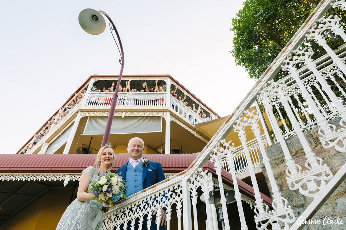 Bride and Groom stand below the balcony of their Como Hotel Wedding as their guests hang over the side cheering!