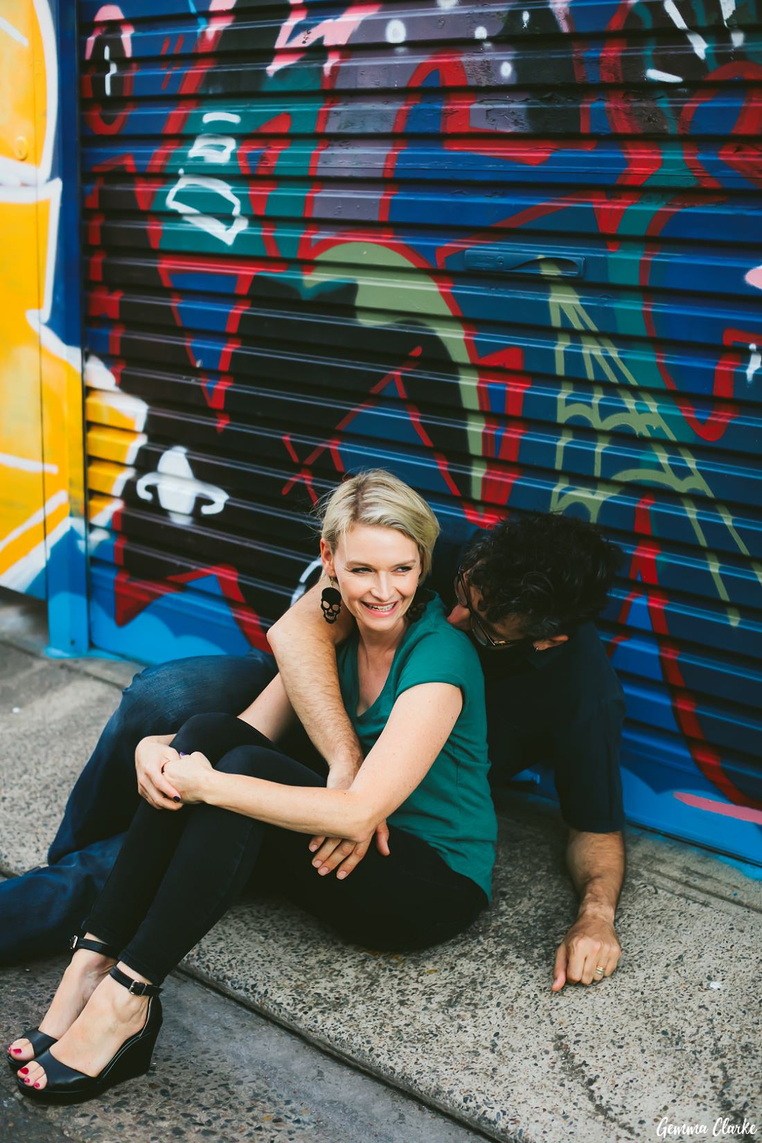 Sitting in front of a colourful graffiti art mural garage at these Newtown Couple Portraits