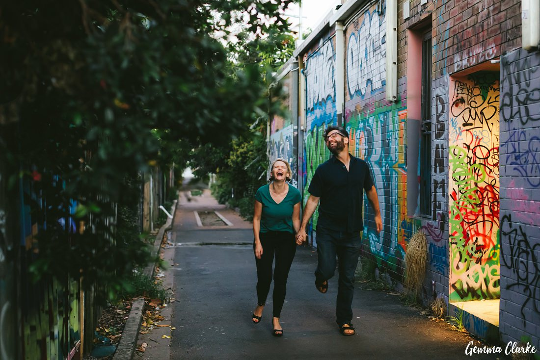 A couple are dancing/skipping down a graffiti filled lane at these Newtown Couple Portraits