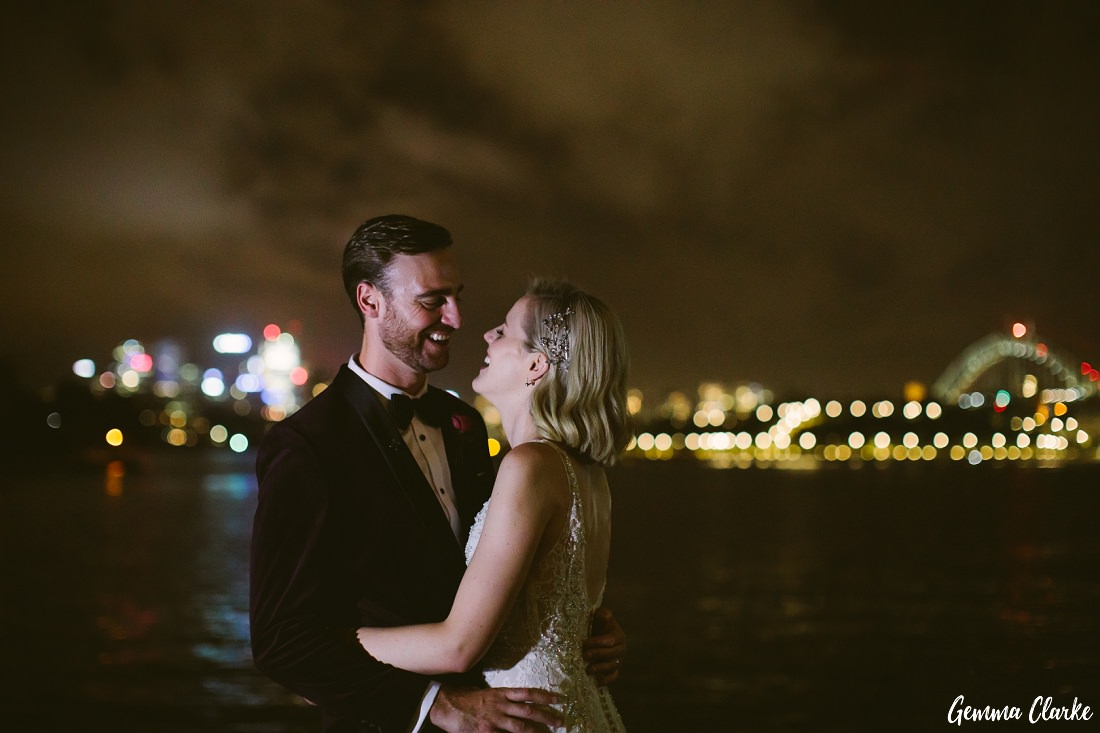Bride and Groom at night in front of the water with Sydney Harbour as the backdrop and the Harbour Bridge lit up at this Cafe Morso Wedding.
