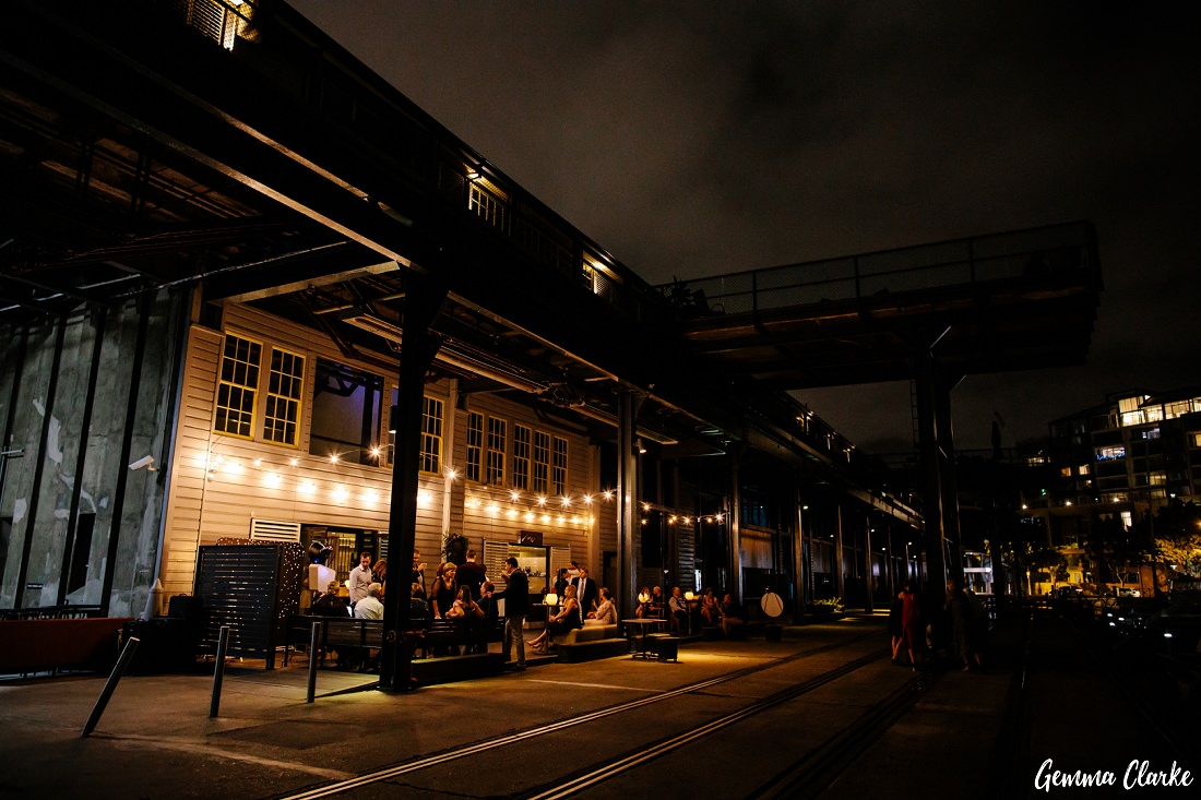 Cafe Morso Wedding on the Pyrmont wharf at night with gorgeous lighting and guests mingling.