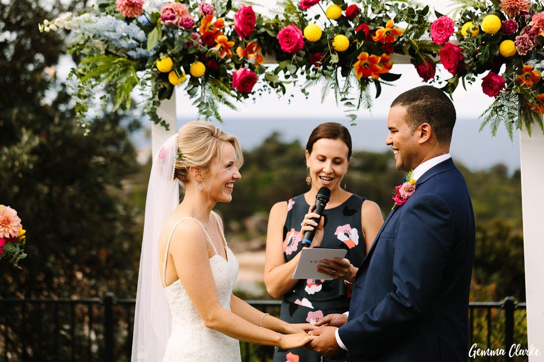 The promises for forever at the brightly decorated arbour at this Freshwater Wedding