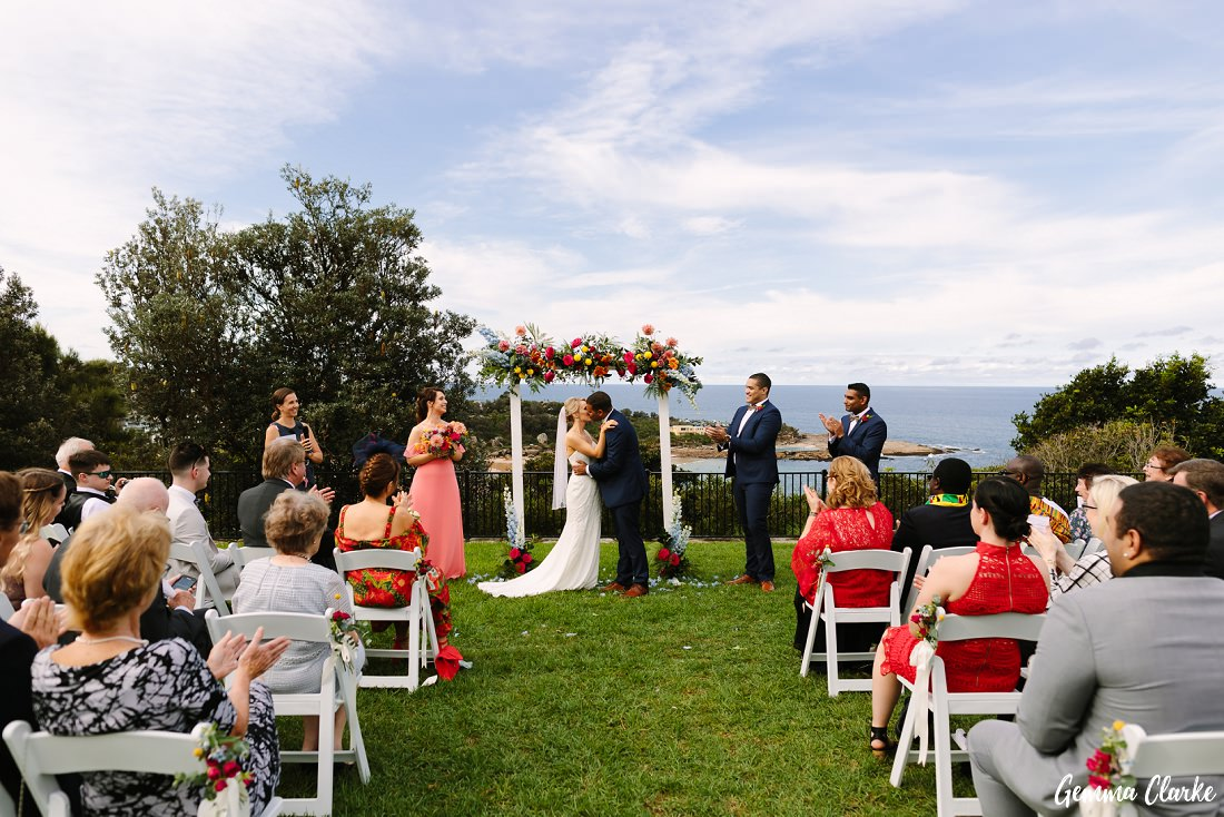 The ceremony kiss at this Freshwater Wedding with lots of bright florals and happy guests!