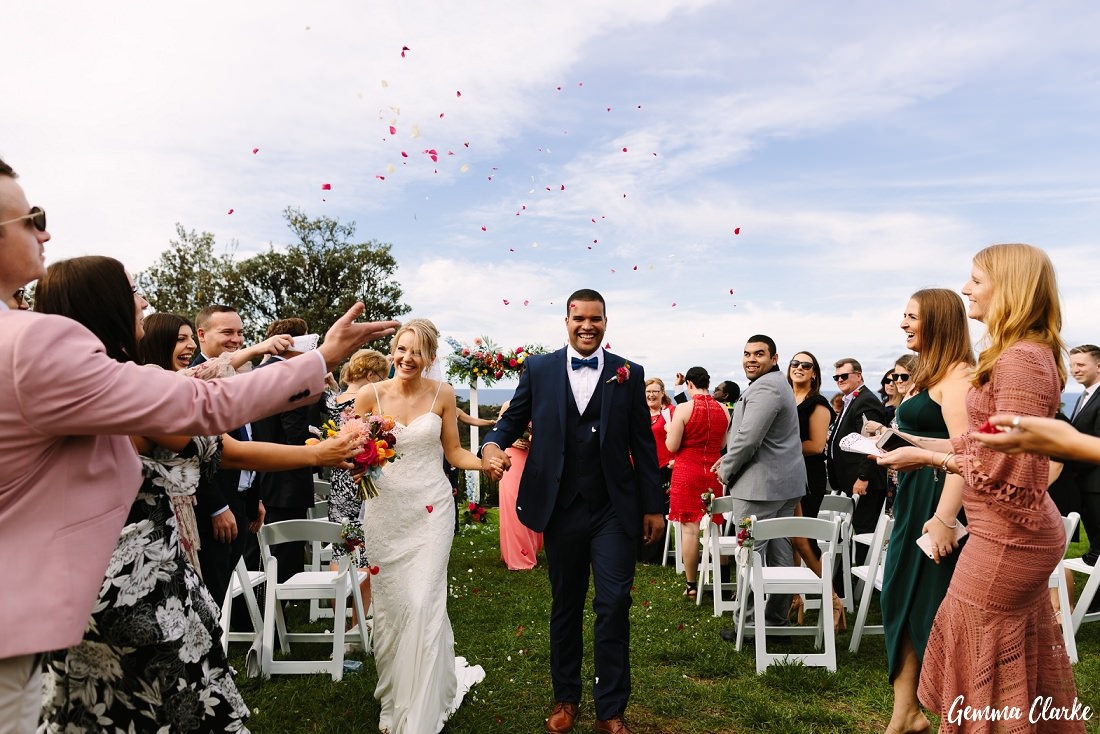 Rose petal confetti and lots of happy faces as Charlotte and Patrick walk back down the aisle together at this Freshwater Wedding
