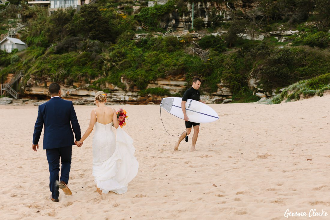 The typical scene on Freshwater Beach, a surfer finished for the day and walking just in front of the bride and groom at this Freshwater Wedding