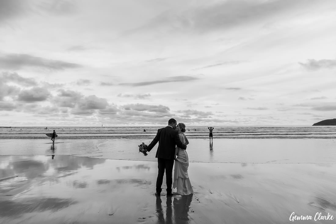 Black and white at an overcast sunset at this Freshwater Wedding with surfers and swimmers in the background