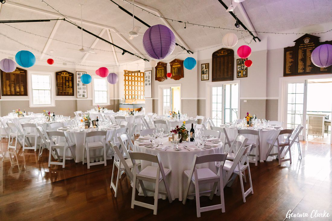 Freshwater Surf Lifesaving Club Reception room set up with white tables and chairs and colourful lanterns for a Freshwater Wedding