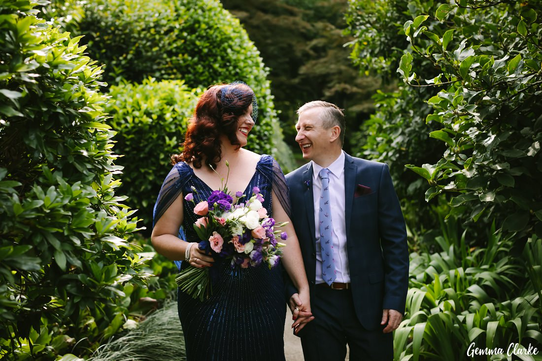 Bride and Groom all smiles through the greenery at their Mount Tomah Botanic Gardens Wedding