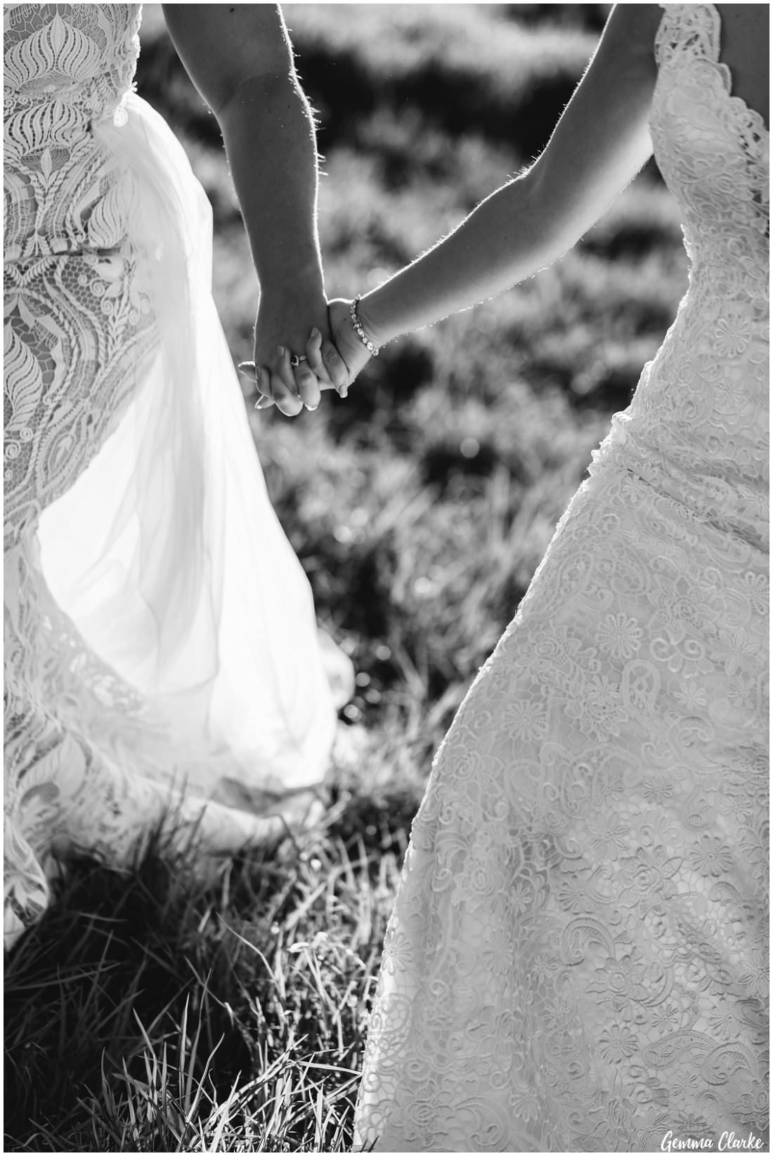 Hand in hand forever, two brides walk across the meadow at their Ottimo House Wedding