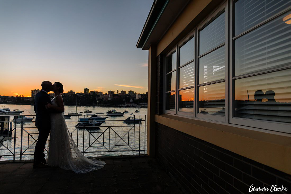 Sunset on the balcony overlooking the water as the bride and groom kiss at this Manly Yacht Club Wedding