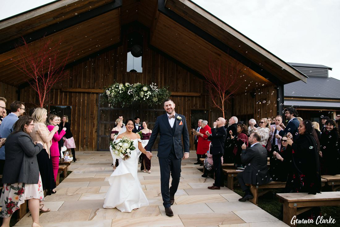 Bubbles being blown as the couple walk back down the aisle at The Stables Wedding
