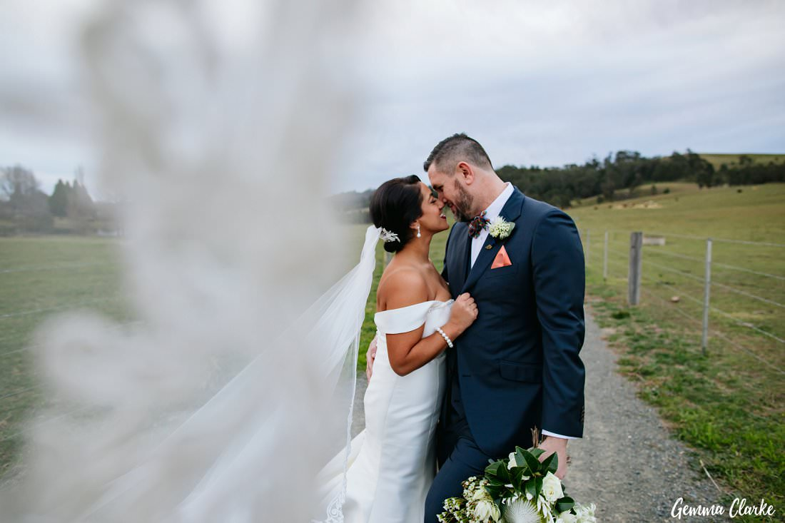The bride's very long veil provided a border for their kissing action at The Stable Wedding