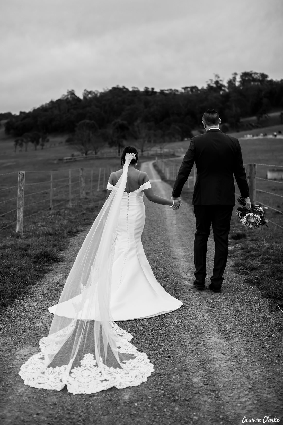 Bridal couple walk down a country road at The Stables Wedding at Bendooley Estate