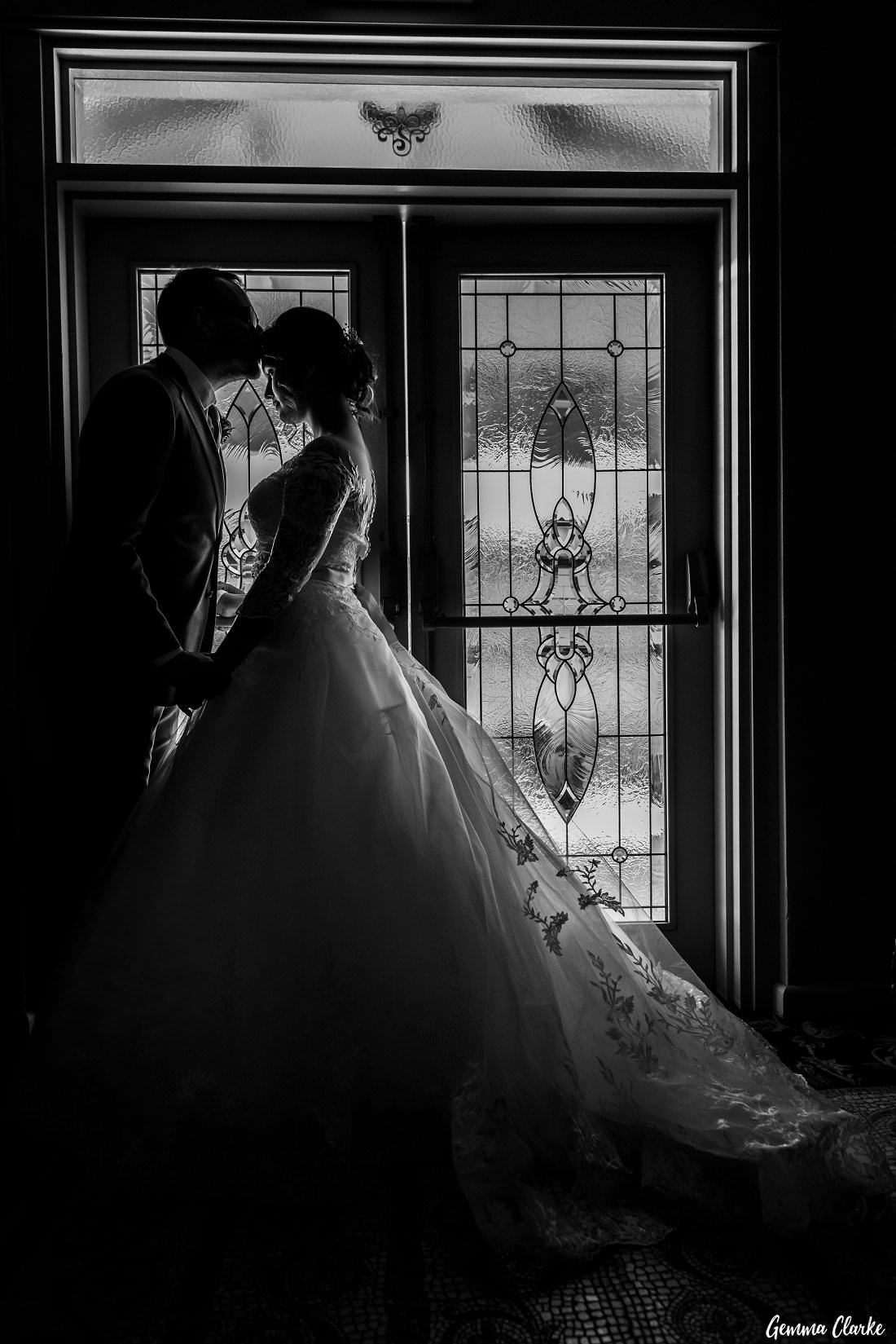Black and white silhouette of bridal couple by the stain glass windows at this Gardens on Forest Wedding