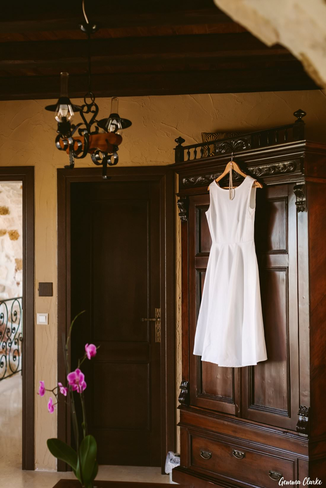 The second wedding dress hangs proudly on antique furniture at this Greek Villa Wedding