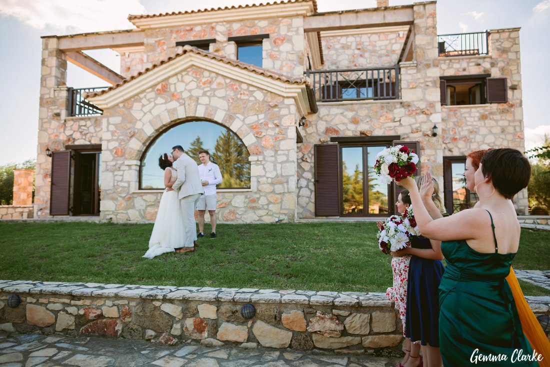 The first kiss as guests cheer them on at this Greek Villa Wedding