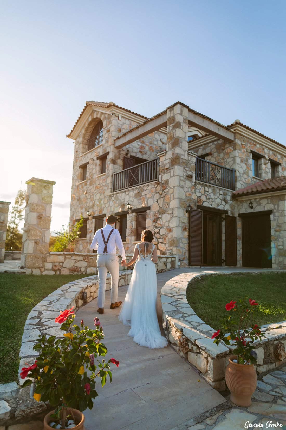 Bride and Groom Walking hand in hand as the sun is going down at this Greek Villa Wedding