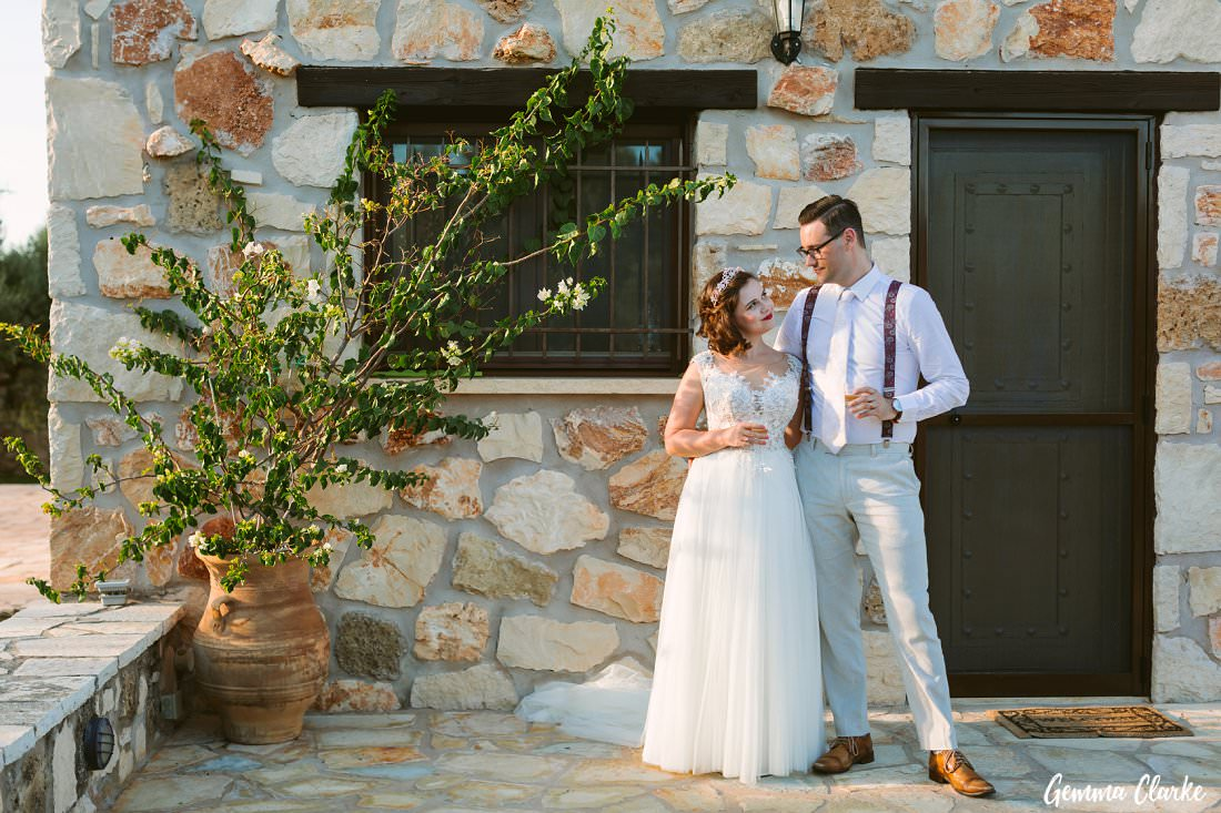 A beautiful stone backdrop as the bride and groom look lovingly into each other's eyes at their Greek Villa Wedding