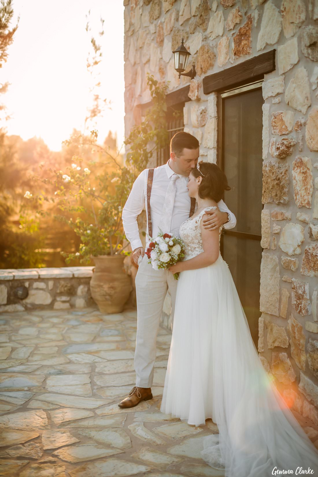 Another beautiful moment as the groom kisses the bride's forehead at their Greek Villa Wedding