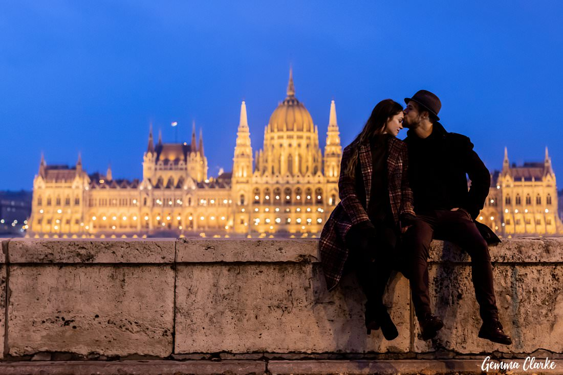 Sitting on a ledge kissing as the blue hour hits the Hungarian Parliament Building in Budapest
