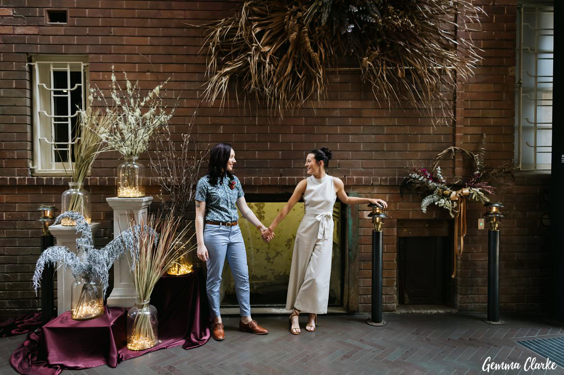 Two brides posing amongst a beautiful display at the Old Clare Hotel before heading to Archie Rose Distillery