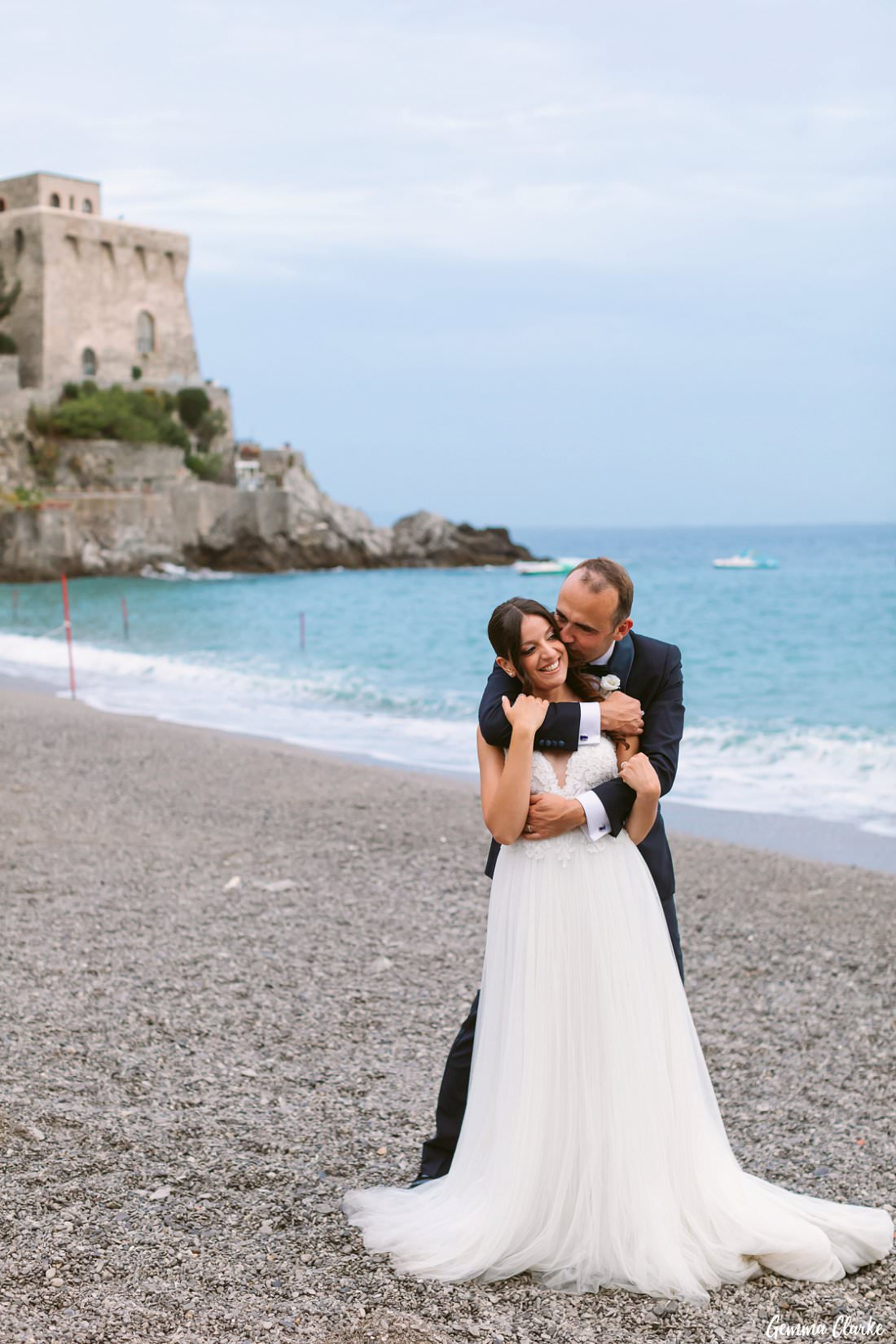 Kisses for the bride whilst on the pebble beach with Torre la Cerniola in the background at this Italian destination wedding