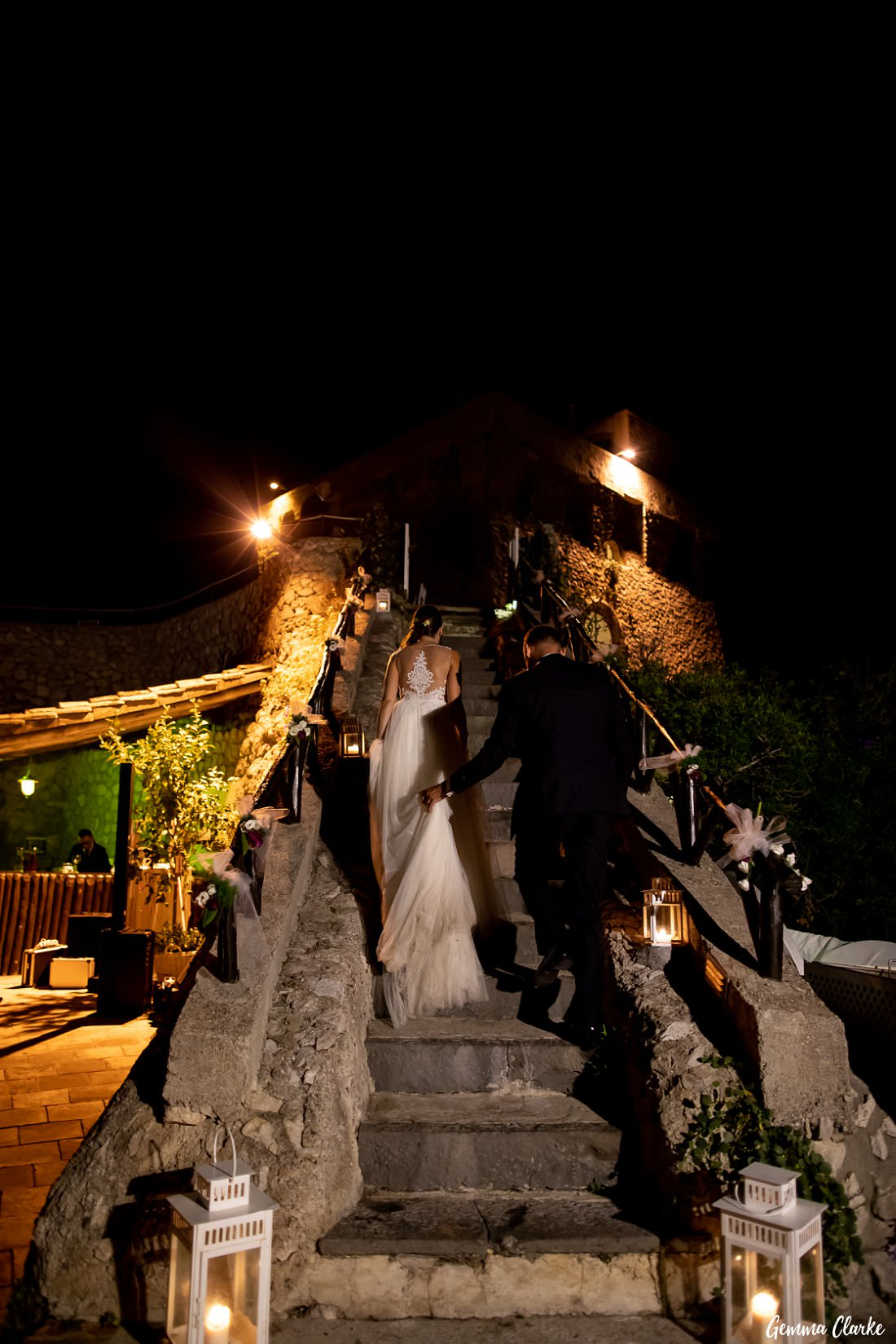 Groom helps the bride with her dress while walking up the Torre la Cerniola stairs at this Italian destination wedding