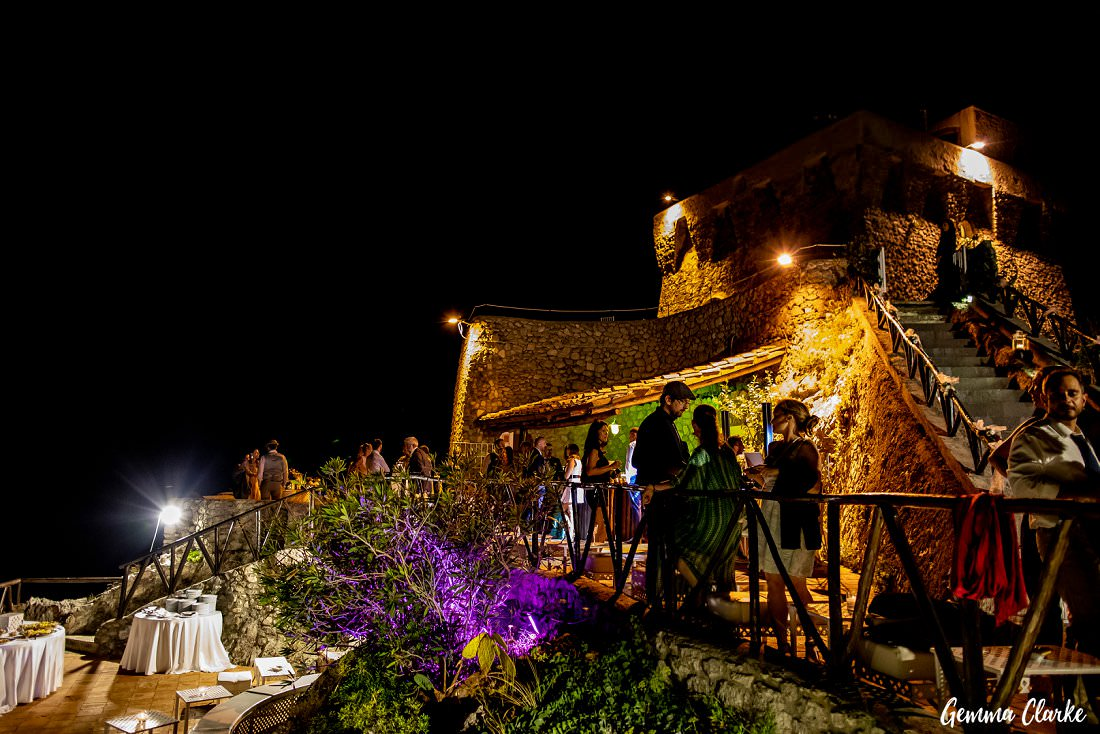 Guests mingle at night at this fort with colourful lights at this Italian destination wedding