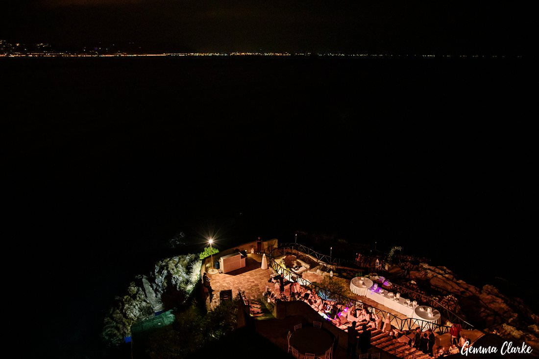 At night over looking the tiered reception wedding party with guests dancing at this Italian Destination Wedding