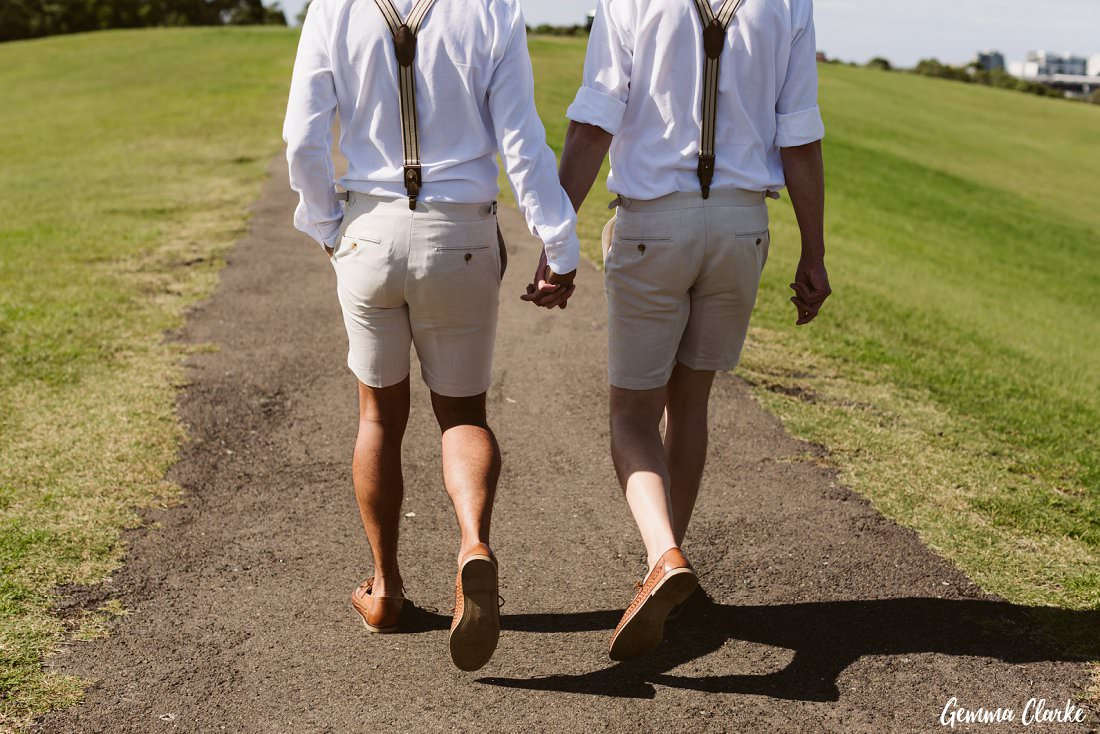 These two grooms walking hand in hand at their Sydney Park wedding