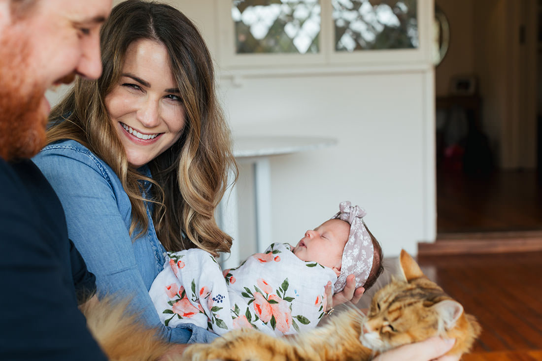 Newborn photos with a feline as well - mum and dad hold both baby and cat in their arms laughing