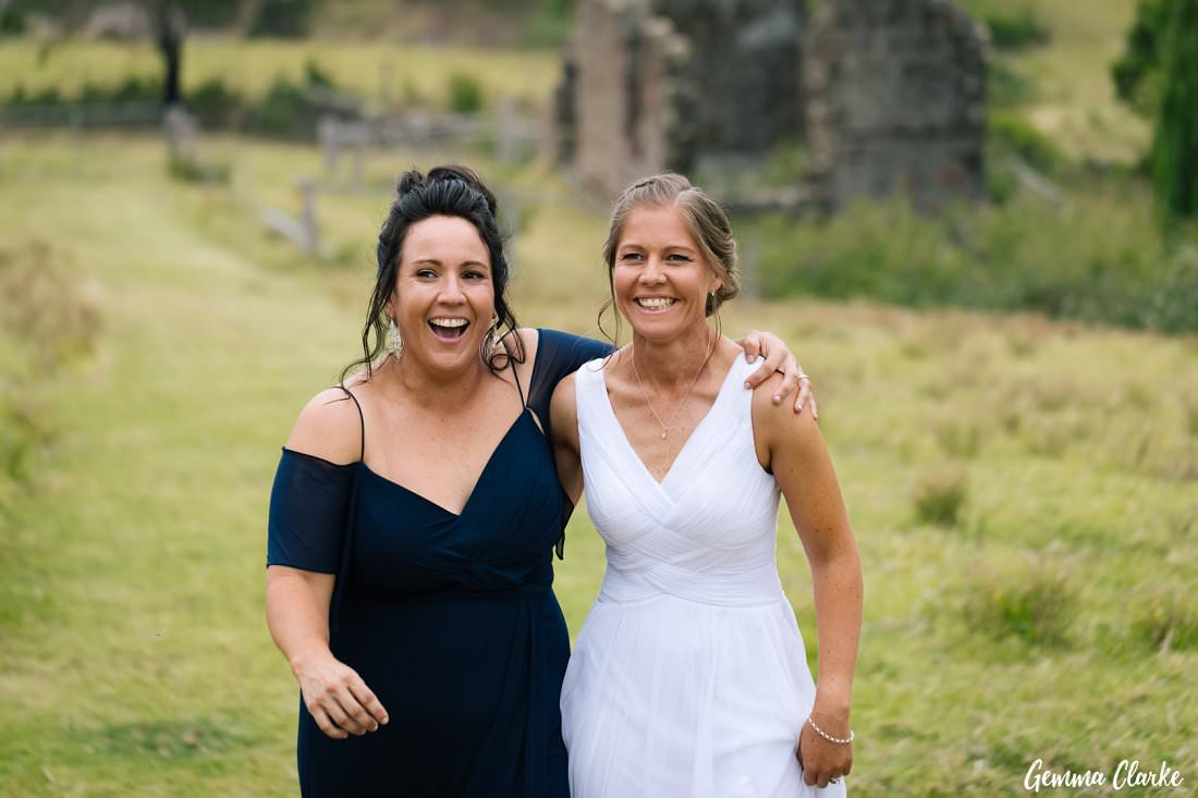 Two wonderful brides walk arm in arm through the Bush Bank paddocks - one bride with a white dress and the other with a navy wedding dress at their Kiama Wedding