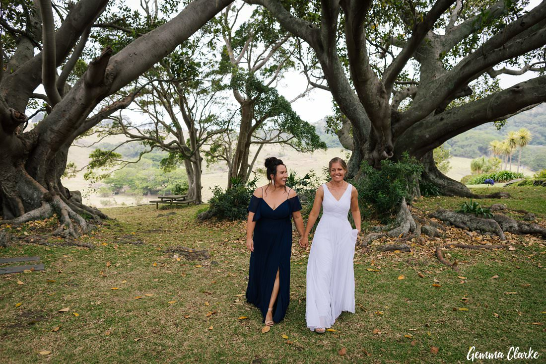 Two brides walking hand in hand among the spectacular fig trees at their Bush Bank Kiama Wedding