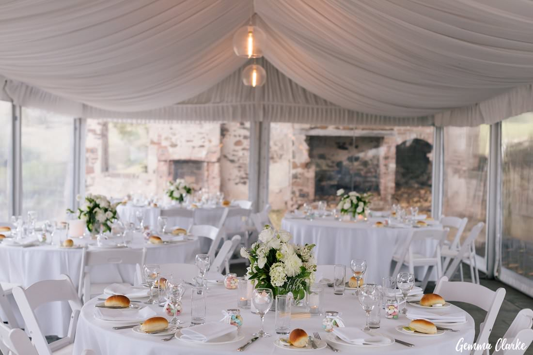 A beautiful white Kiama wedding setup at Bush Bank with a mix white floral table decorations and sugared almonds.