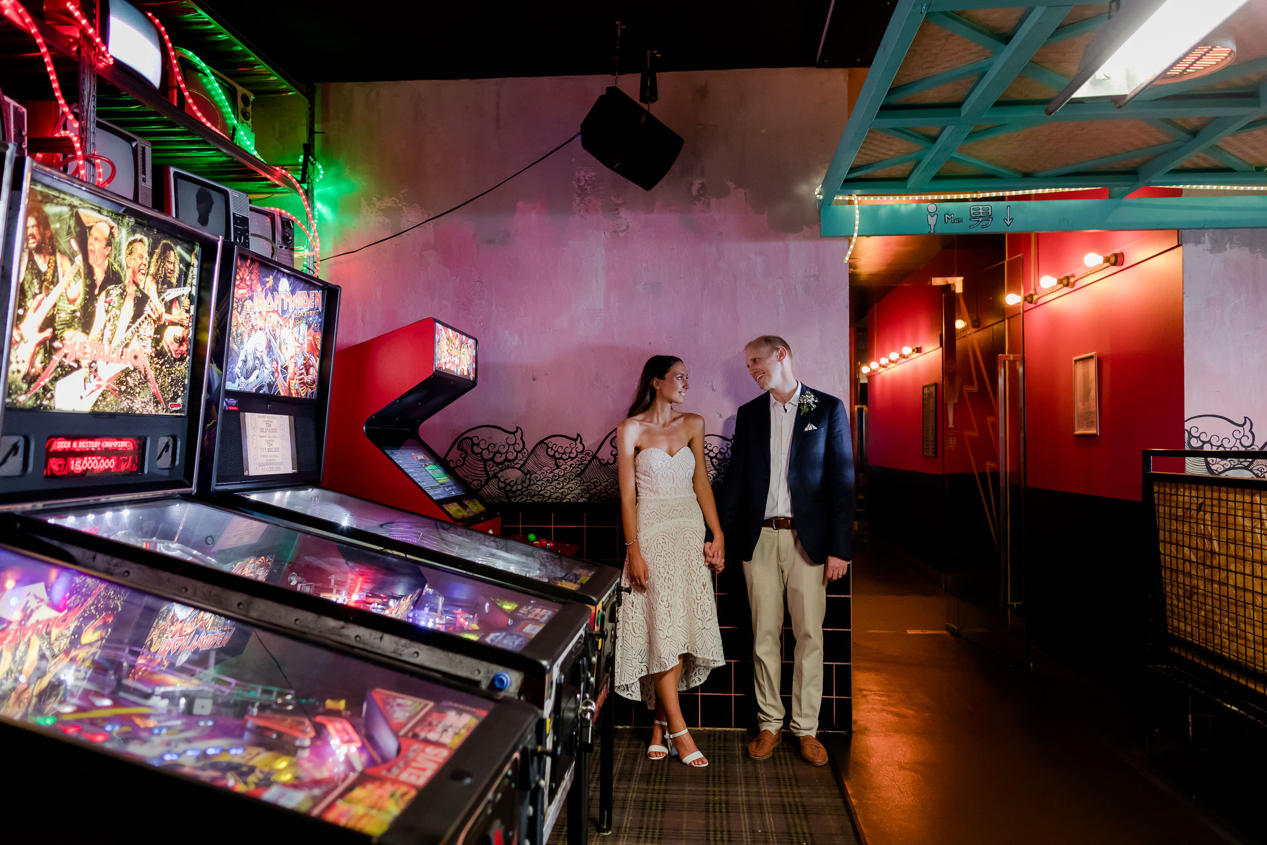 Couple stand by the pinball machines at Daniel San Bar