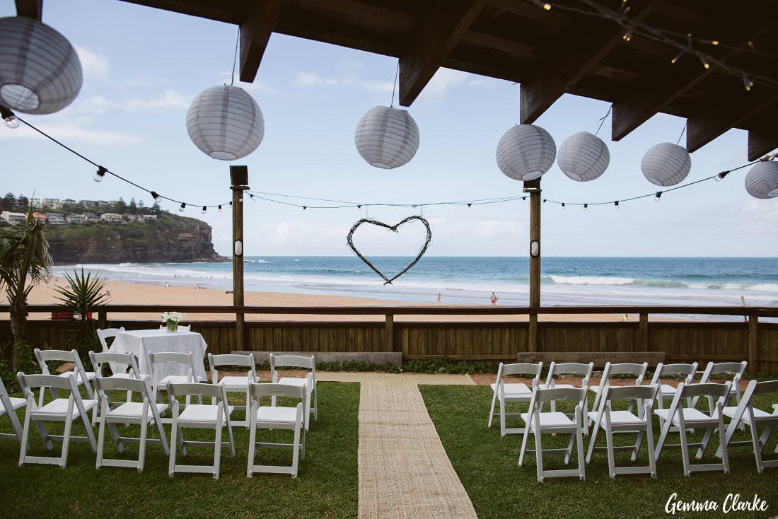 Stunning outlook through hanging lanterns over this Bilgola Beach wedding ceremony setup