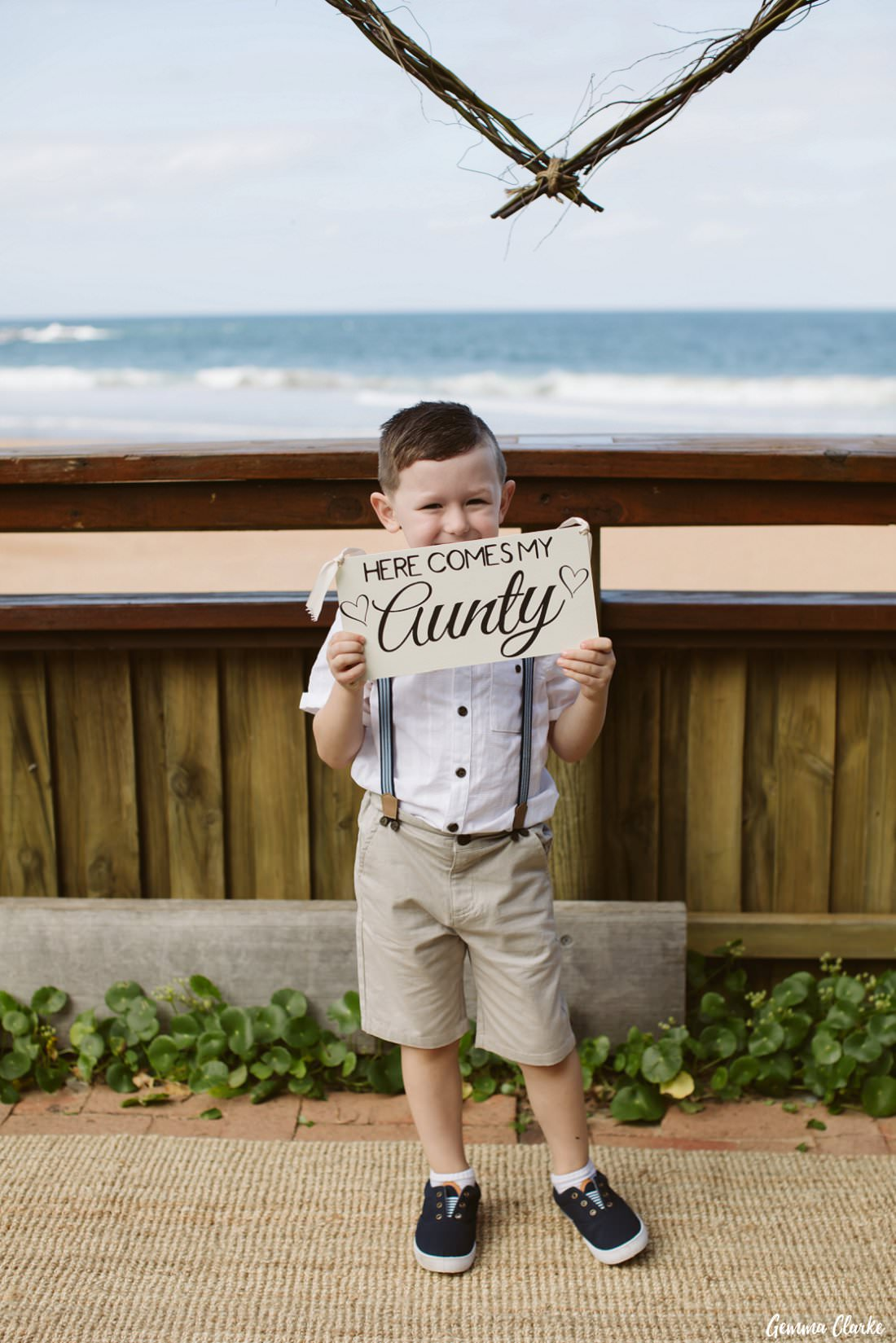 Cute page boy holding up 'Here Comes my Aunty' sign and ready to walk down the aisle at this Bilgola Beach Wedding
