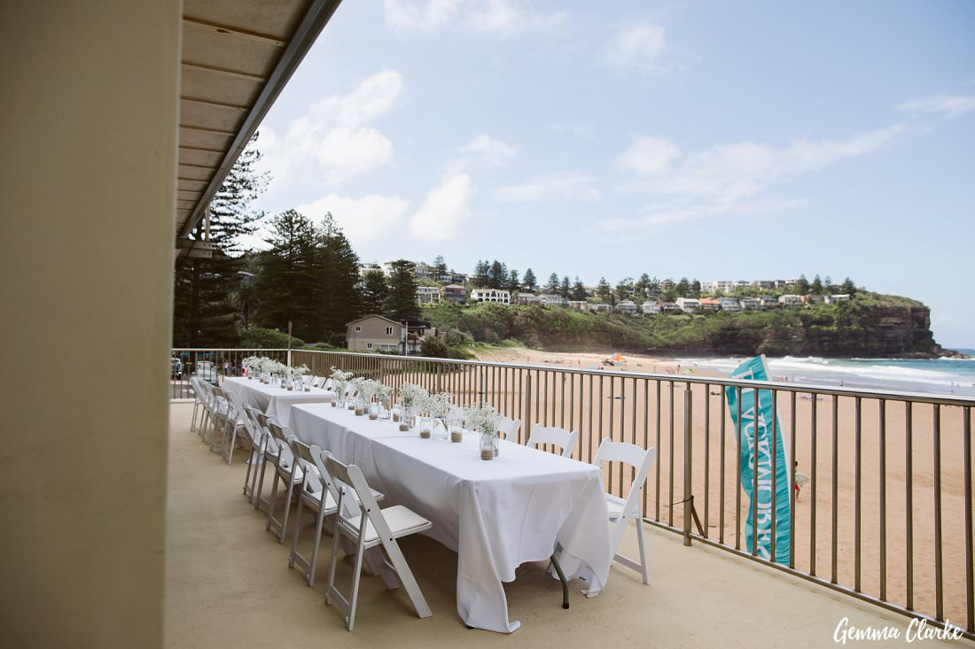 Relaxed white wedding reception set up on the blacony of the surf life saving club overlooking the sands at this Bilgola Beach Wedding