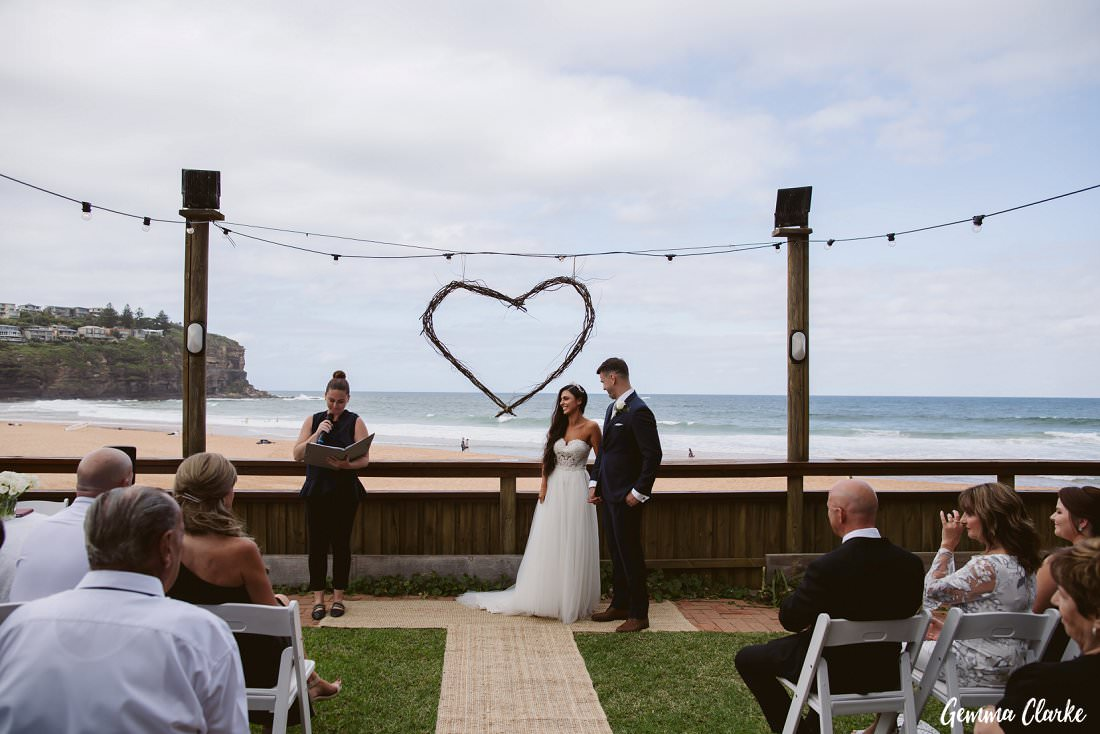 The couple standing at the end of the aisle in front of a heart made of branches at their Bilgola Beach Wedding