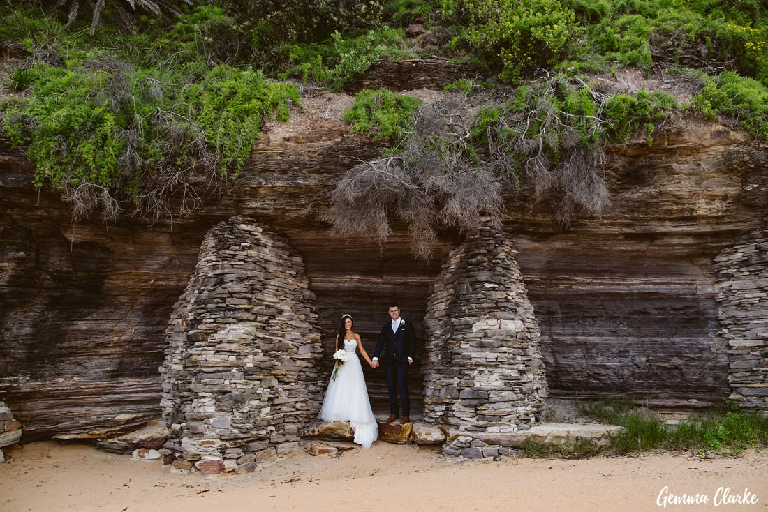 Amongst the rock formations the bride and groom hold hands with the greenery falling from above at their Bilgola Beach Wedding