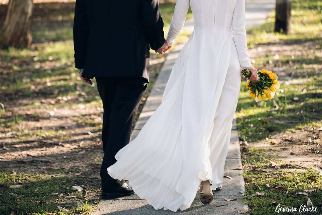 A close of the detail of Tracy's amazing Vietnamese inspired wedding outfit and walking with her groom