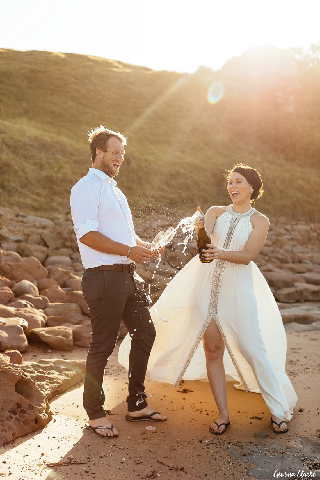 Bride and groom pop bubbly to celebrate their Bulli elopement on Sandon Point Beach with the sun streaming through!