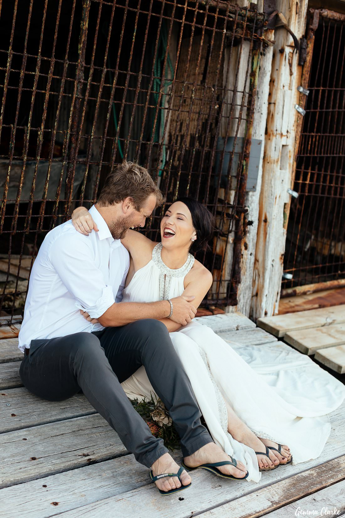 Gemma and Hayden sit in front of the boatshed at Sandon Point and have a laugh at their Bulli elopement