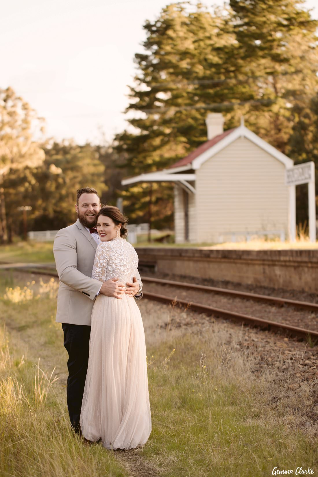 Bride and Groom cuddle by the old railway station near their Buxton wedding location